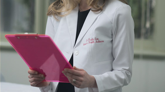 A woman in a doctor's coat holding a pink clipboard