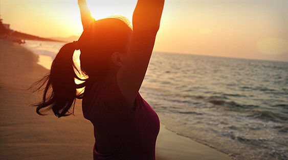 A woman looks towards the ocean at sunset and raises her arms above her head