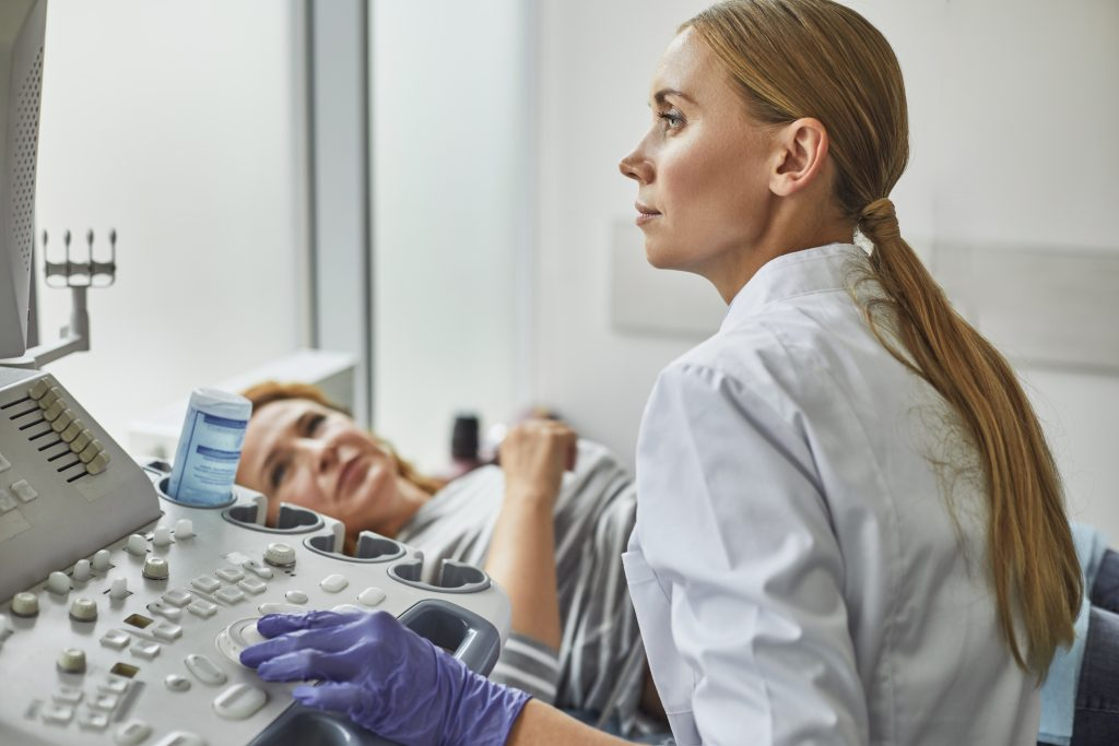 Doctor checking woman pregnancy during sonography procedure